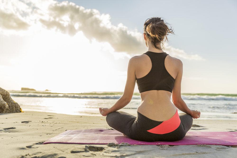 tri.balance Stretching am Strand, Dehnübung, Dehnen der Oberschenkelinnenseiten, Fit im Urlaub